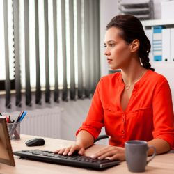 Executive businesswoman in workplace office working on finance corporate project. Successful concentrated employer with busy carreer sitting at desk in office using modern pc.